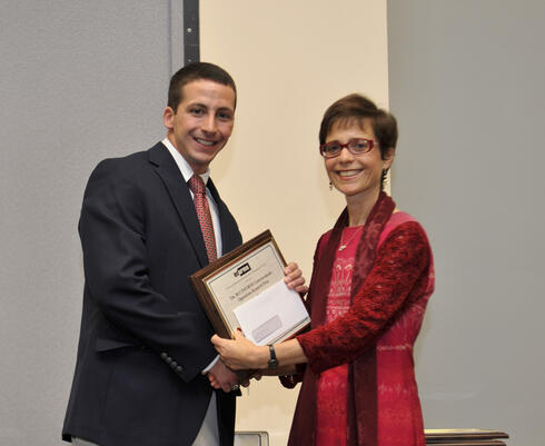 Matthew Robinson receiving his award from INFORMS President Rina Schneur