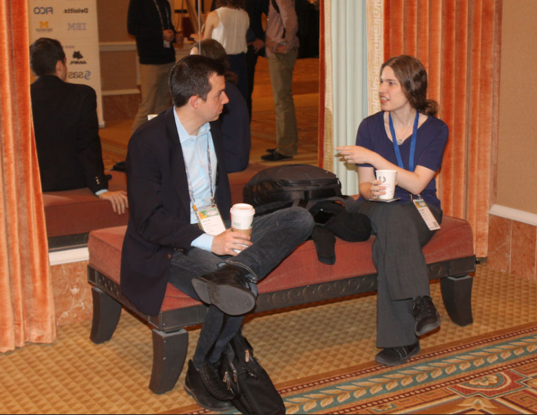 Two Members discussing something on a bench, out of the way at the 2017 Analytics Conference