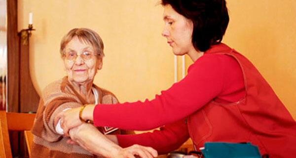 Health Care Worker takes Elderly patient's blood pressure