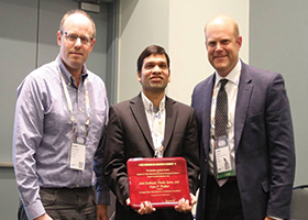 Amit Kothiyal (center) receives the Publication Award.