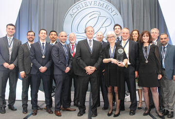 "Jean Kiddoo (holding award) and the rest of the FCC's Edelman Award team are all smiles after winning the ""Super Bowl of O.R."" Former INFORMS presidents Michael Trick (sixth from left) and Karla Hoffman (third from right) were key members of the team."