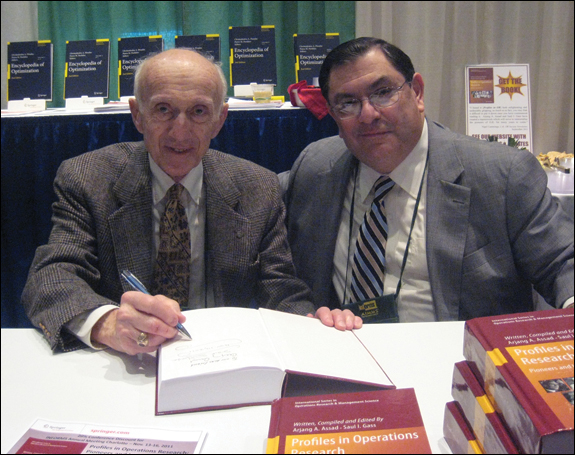 "Saul Gass and Arjang Assad sign copies of their new book, ""Profiles in Operations Research: Pioneers and Innovators."""