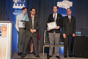 Ruben Proano (left) presents the Doing Good with Good O.R. Student Paper honor to Eoin O'Mahony of Cornell University