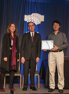 Aurelie Thiele (left) presents the Undergraduate Operations Research Prize to Hongfan Chen (right) as INFORMS President Steve Robinson (center) looks on.